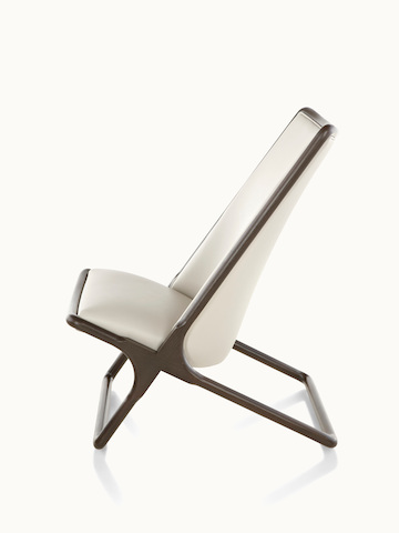 Side view of a Scissor lounge chair with ivory-colored leather upholstery and a wood frame in a dark finish.