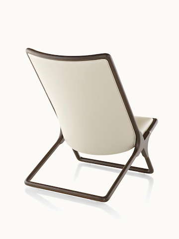 A Scissor lounge chair with ivory-colored leather upholstery and a wood frame in a dark finish, viewed from behind at an angle.