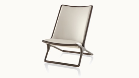 Angled view of a Scissor lounge chair with ivory-colored leather upholstery and a wood frame in a dark finish.