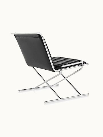 A Sled lounge chair with ribbed black leather upholstery and an X-shaped steel frame, viewed from behind at an angle.
