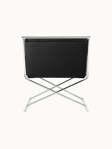 A Sled lounge chair with black leather upholstery and an X-shaped steel frame, viewed from behind.
