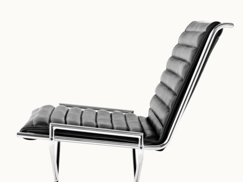 Close-up on the ribbed seat and back of a Sled lounge chair with black leather upholstery, viewed from the side.