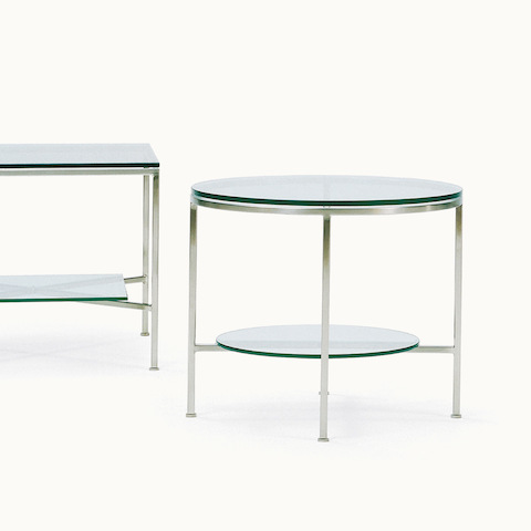 Partial view of a rectangular glass occasional table next to a full view of a round glass table. Select to go to the Slimline Tables product page.