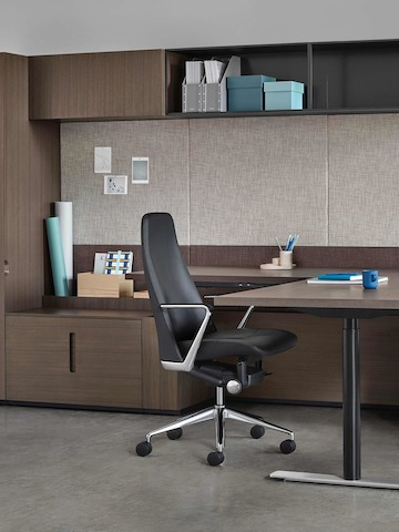 An executive office featuring a black leather Taper office chair and Geiger Rhythm Casegoods with a peninsula desk.