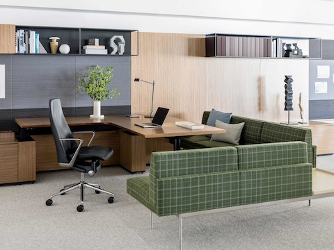 An executive office featuring a Taper office chair in black leather upholstery and Tuxedo Component Lounge Seating in green plaid fabric.