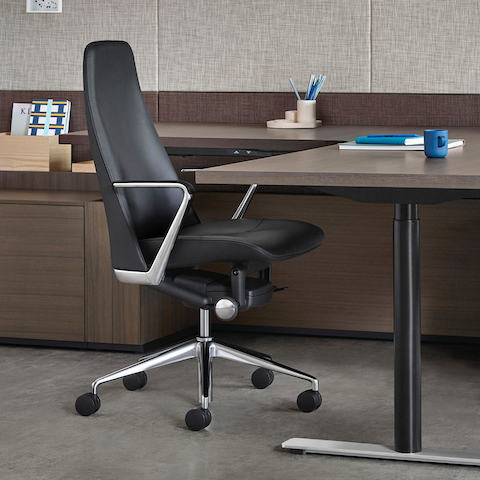 Partial view of an executive office featuring a black leather Taper office chair.