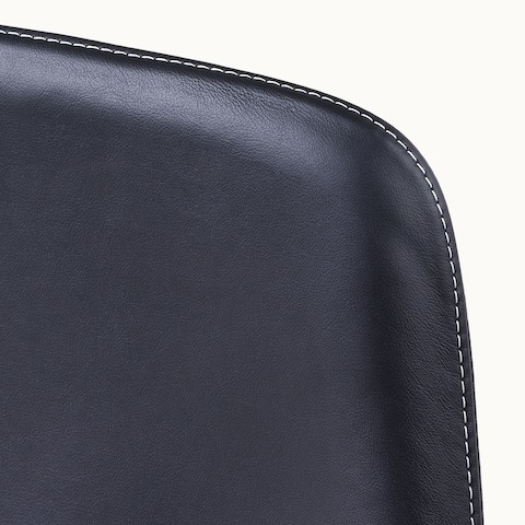 Close-up of an upper corner on the back of a Taper office chair, showing the single stitch option with constrasting thread.