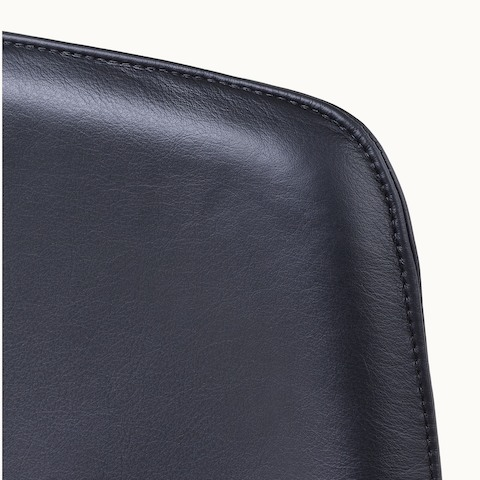Close-up of an upper corner on the back of a Taper office chair, showing the lapped-edge stitch option.