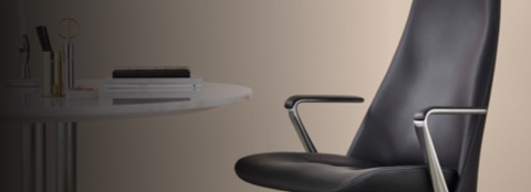 Angled view of the seat, arms, and lower back of a black leather Taper office chair.