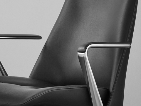 Angled view of the seat, arms, and back of a black leather Taper office chair.