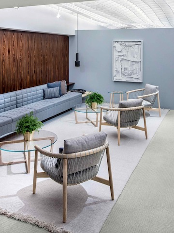 A lounge featuring a light blue Tuxedo Classic Lounge Seating sofa, three light gray Crosshatch Chairs, and three round Loophole occasional tables.
