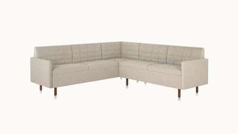 A quilted Tuxedo Classic sectional upholstered in bone-colored fabric.