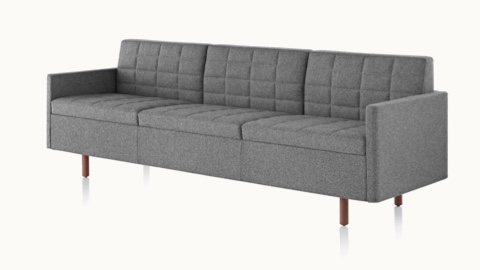 Angled view of a Tuxedo Classic sofa with dark gray quilted upholstery.