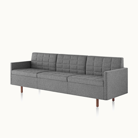 Angled view of a Tuxedo Classic sofa with dark gray quilted upholstery. Select to go to the Tuxedo Classic Lounge Seating product page.