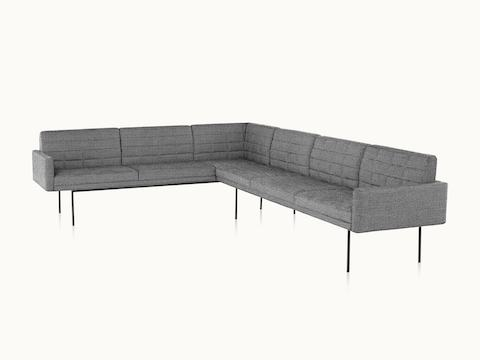 A quilted Tuxedo Component sectional upholstered in gray fabric.