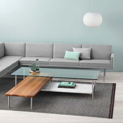 A non-quilted Tuxedo Component sectional upholstered in light gray fabric partially surrounds an L-shaped Layer coffee table.