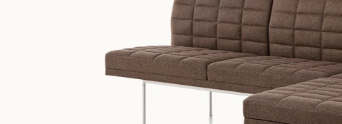 Partial view of a quilted Tuxedo Component corner unit upholstered in brown fabric.