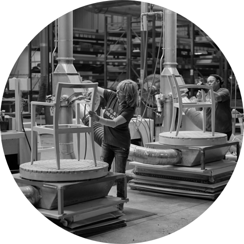 A circular image of two Geiger employees assembling side chairs in a manufacturing plant.
