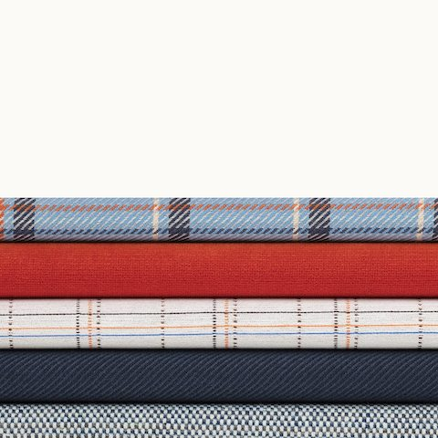 A stack of five textiles from Geiger's Brighton Collection in various colors and patterns. Select to go to the Brighton Collection page.