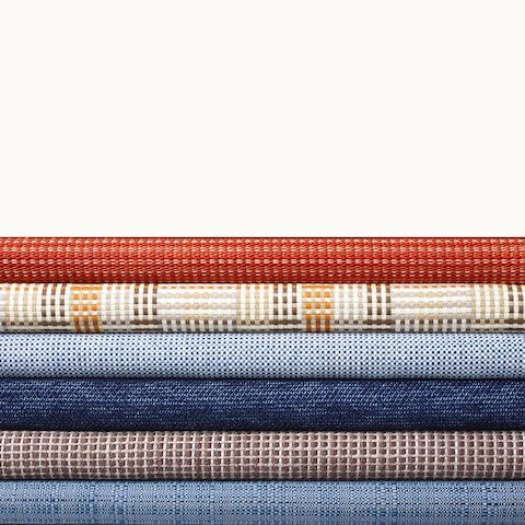 A stack of six textiles from Geiger's Framework Collection in various colors and patterns. Select to go to the Framework Collection page.