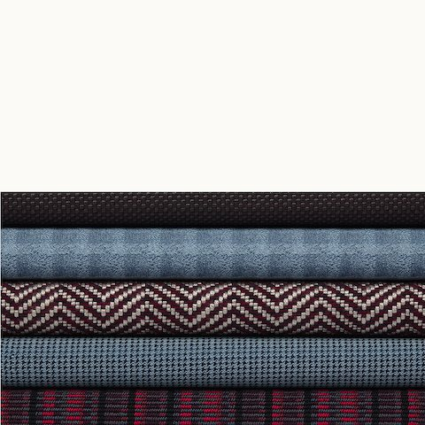 A stack of five textiles from Geiger's Sartorial Collection in various colors and patterns.