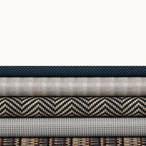 A stack of five textiles from Geiger's Sartorial Collection in various colors and patterns. Select to go to the Sartorial Collection page.
