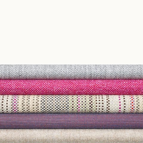 A stack of five textiles from Geiger's Savona Collection in various colors and patterns.