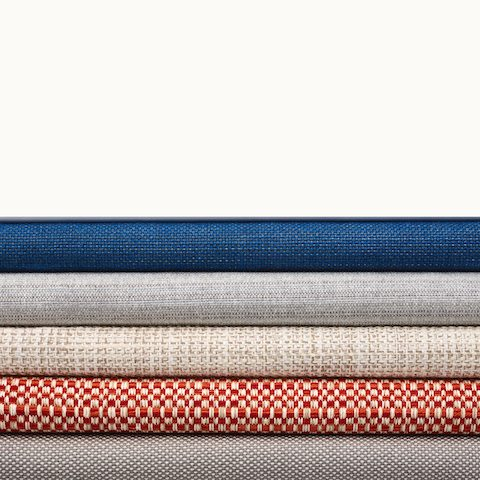 A stack of five textiles from Geiger's Solene Collection in various colors and patterns.