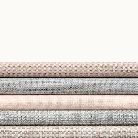 A stack of five textiles from Geiger's Solene Collection in various colors and patterns. Select to go to the Solene Collection page.