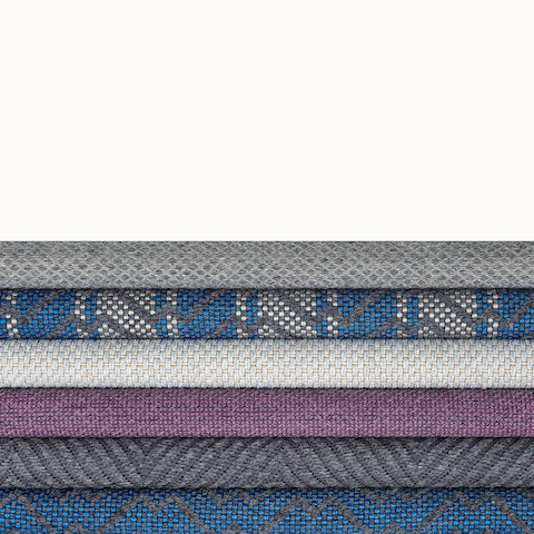 A stack of six gray, blue, and purple textiles from the Taconic Collection.