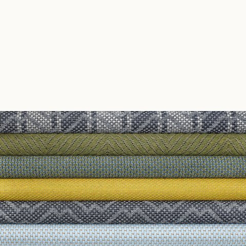 A stack of six yellow, green, and blue-hued textiles from the Taconic Collection. Select to go to the Taconic Collection page.